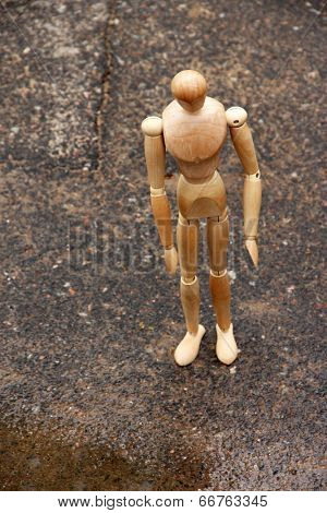 Wooden pose puppet under rain, outdoors