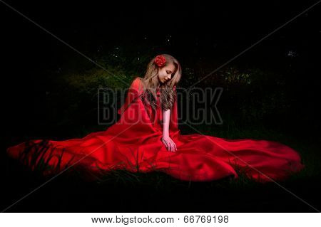 beautiful woman with red cloak in the woods by night