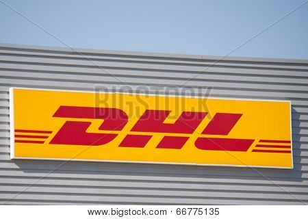 VALENCIA, SPAIN - JUNE 15, 2014: A DHL company sign at its depot in Valencia. DHL is a world wide courier company that operates in 220 countries with over 285,000 employees.