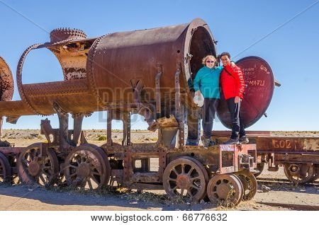 Couple of tourists visiting Cementerio de trenes (Train Cemetery), Salar de Uyuni, Bolivia