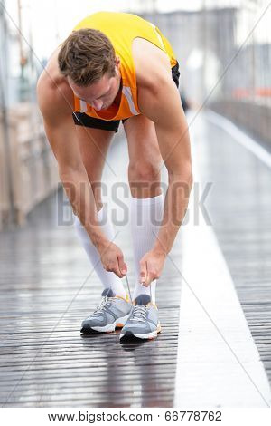 Runner man tying laces on running shoes, New York City on Brooklyn Bridge. Male athlete runner and feet closeup. Fitness model wearing compression socks.