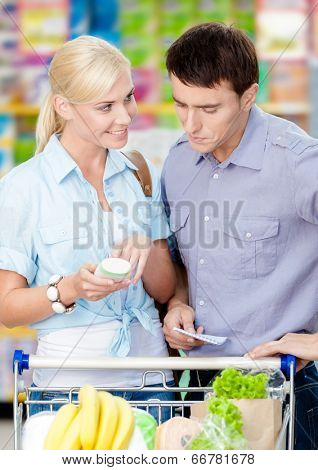Couple discussing the shopping list and chosen products standing near the cart full of food
