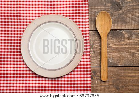 Plate on wooden table with red checked tablecloth