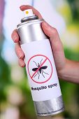 pic of mosquito repellent  - Hand holding mosquito spray on nature background - JPG