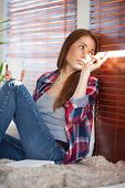 pic of jalousie  - Young woman on sofa at home and looking through jalousie - JPG