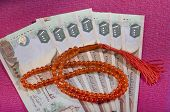 pic of dirham  - UAE dirham currency notes and a rosary  - JPG