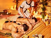 picture of stone-therapy  - Woman and man getting stone therapy massage in bamboo spa - JPG