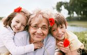 stock photo of grandmother  - Closeup summer portrait of happy grandmother with grandchildren outdoors
