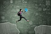 image of gap  - Female student jumping in classroom through gap on the blackboard