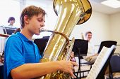 stock photo of orchestra  - Male Pupil Playing Tuba In High School Orchestra - JPG