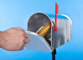 picture of mailbox  - Man opening his mailbox to remove mail inside close up of his hand on the open door against a blue sky - JPG