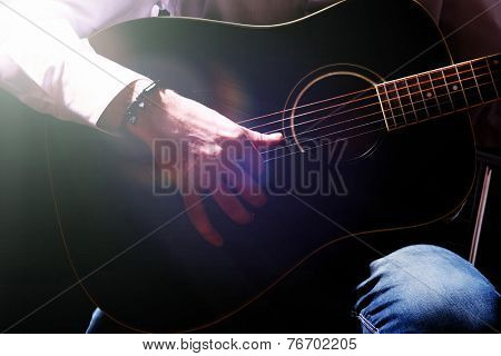Young musician playing acoustic guitar, on dark background