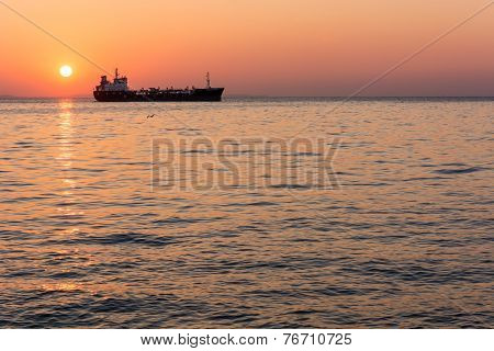 Sunset At The Sea With Cargo Ship
