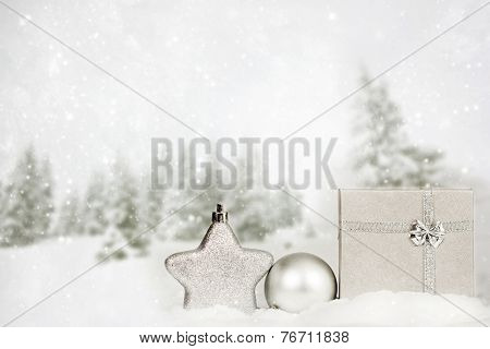 Silver Christmas decorations and gift box in the snow, snow cowered pine trees in the background