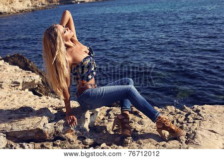 Sexy Girl With Luxurious Blond Hair In Jeans Posing On Beach