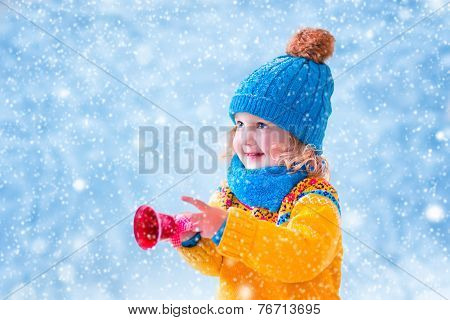 Beautiful Little Girl Catching Snow Flakes