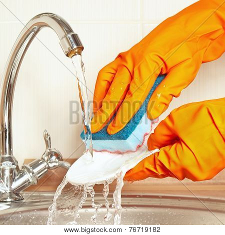 Hands in rubber gloves with sponge wash dirty dishes under running water