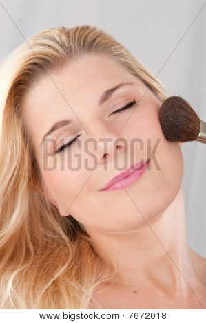 beautiful woman with pure healthy skin applying powder on her face