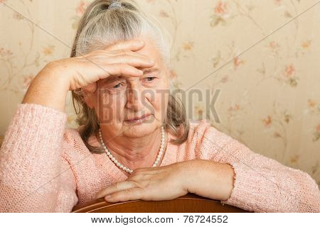 Elderly woman grieves at home.