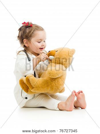 child dressed as doctor playing with toy over white