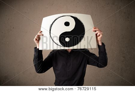 Businessman holding a paper with a yin-yang symbol on it in front of his head