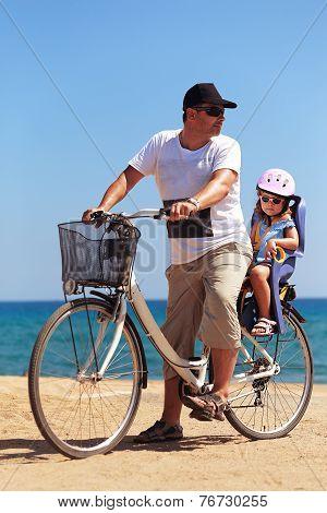 Happy Man And Kid Girl Biking On Blue Sea Background