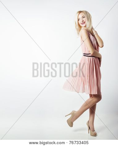 beautiful sexy elegant striking blonde woman with bright makeup in pink dress