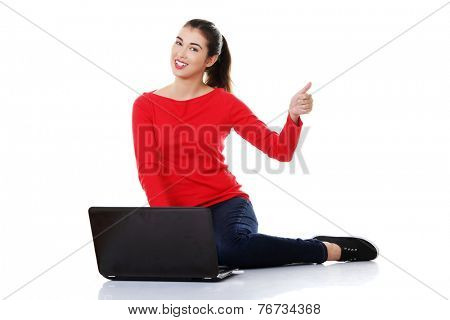 Woman sitting cross-legged with laptop pointing up.