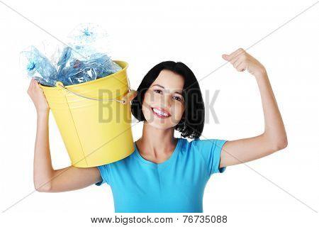 Happy woman holding bucket of plastic rubbish.