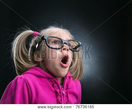 Little astonished girl in funny big spectacles