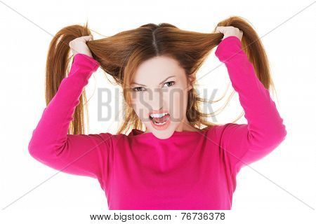 Frustrated and angry woman pulling her hair.