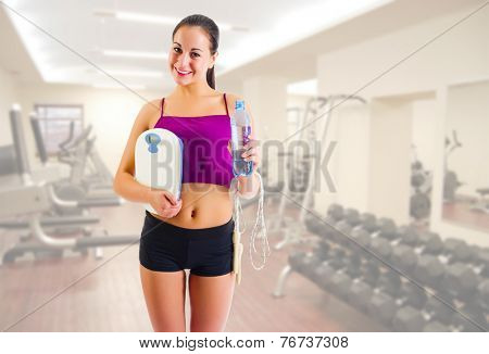 Young sporty girl with water bottle and scales at gym club