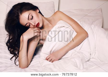 Sensual Woman With Dark Hair And Bright Makeup Lying In Bed