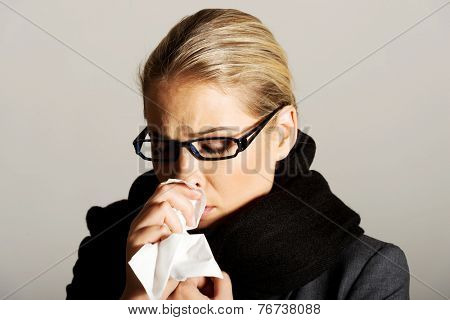 Beautiful woman sneezing because of flu