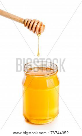 Opened Honey Jar On White Background With Wooden Honey Dipper On Top And Drop Honey