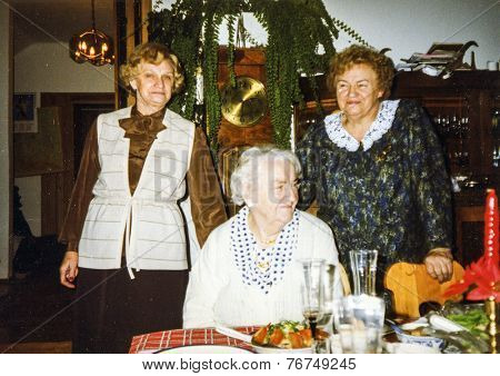 Vintage photo of elderly woman and her adult daughters during a Christmas dinner, eighties