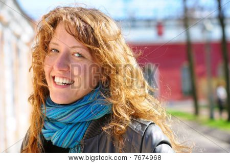 Happy Beautiful Woman Is Looking At Camera At City Street