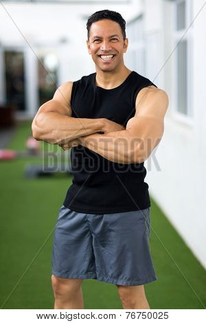 sportive middle aged man with arms crossed in gym