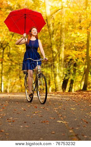 Girl Relaxing With Bicycle Red Umbrella In Autumn Park