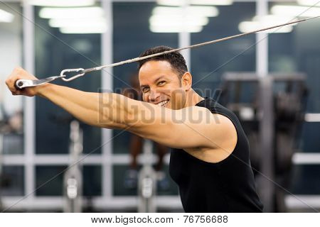 side view of mid age man working out with pull-down machine