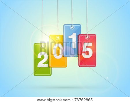 Stylish colorful hanging tags decorated with text 2015 on shiny blue background for Happy New Year celebrations.