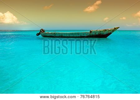 Wooden boat floating on the clear turquoise water of Zanzibar island