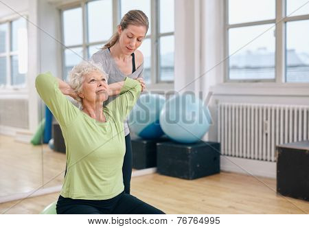 Trainer Helping Senior Woman Exercising
