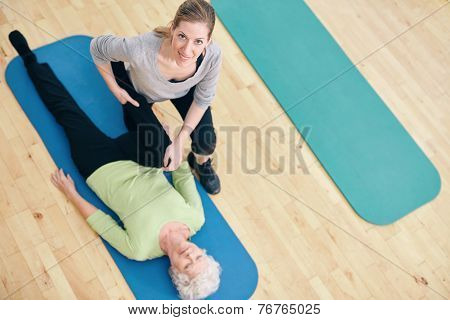 Female Trainer Helping Senior Woman Do Leg Stretches At Rehab