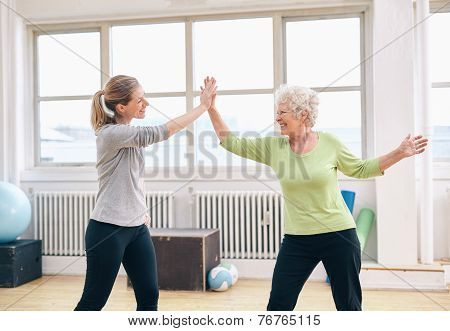 Senior Woman Giving High Five To Her Coach At Gym