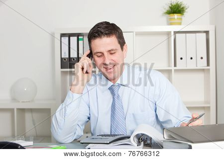 Businessman Talking Through Phone At His Office