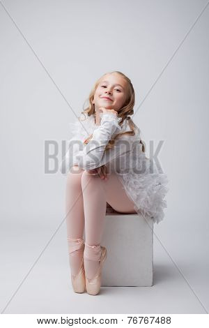 Coquettish little ballerina posing at camera