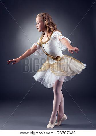 Cute little ballerina dancing in studio