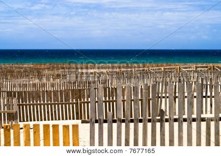 Sand beach of Tarifa with wooden sand-fences against blue sky and aquamarine sea