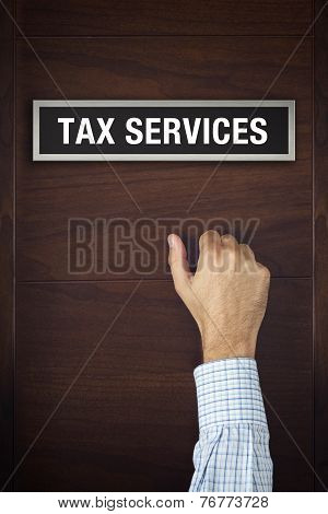 Hand Is Knocking On Tax Services Door